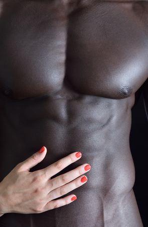 fondling: A white womans hand on a muscular belly of a black man Stock Photo