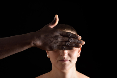 a hand covering  eyes of caucasian woman on black
