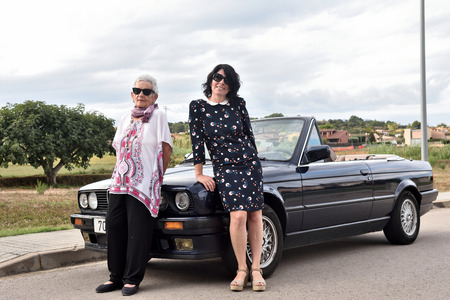 portrait of two women leaning on a car