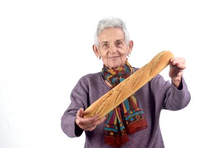 senior woman eating bread on white background