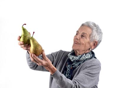 senior woman eating pear on white