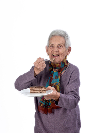 Older woman eating a piece of cake Banco de Imagens
