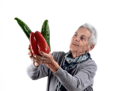 senior woman eating pepper on white