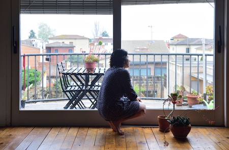 a sad woman looking out the window at home