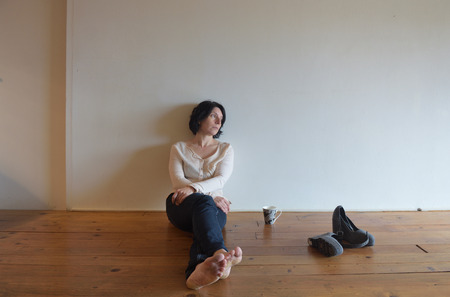 a sad woman on the wooden floor of her house Banque d'images