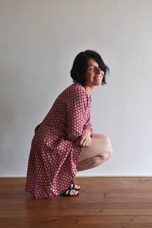 woman sitting squatting in front of ura wall Foto de archivo
