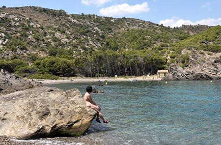 Nudist woman on a beach Cala Taballera, Cap de Creus, Spain Stockfoto