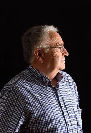 Portrait of a senior man with black background