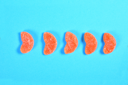 group of jelly candies piece of orange fruit bottles on blue background 免版税图像