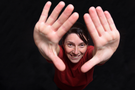 woman two hands up on black background