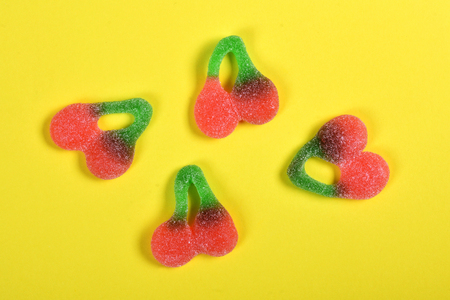 group of jelly candies cherries on yellow background