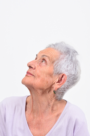 portrait of senior woman looking up on white background