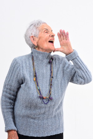 Senior woman putting a hand in mouth and is screaming on white background