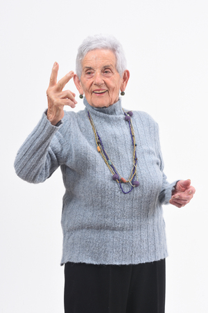 Older woman making the victory sign on a white background Stock Photo