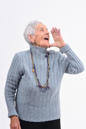 Femme âgée mettant une main dans la bouche et crie sur fond blanc