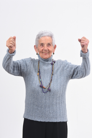 senior woman raising her arms and smiling in victory sign on white background