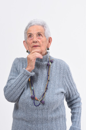 thoughtful senior woman looking up on a white background Zdjęcie Seryjne - 127457502