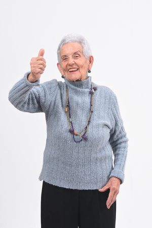 older woman with thumbs up and smile on white background Foto de archivo - 127457503