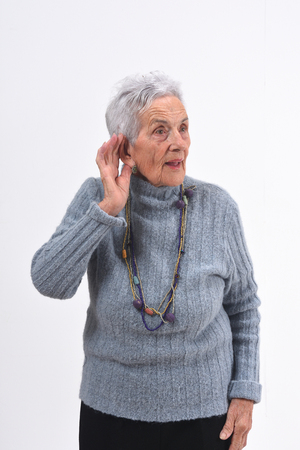 senior woman putting a hand on her ear because she can not hear on white background Zdjęcie Seryjne - 127457533