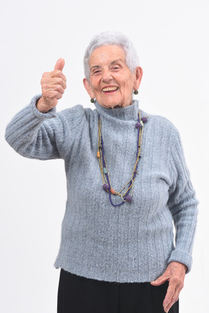 older woman with thumbs up and smile on white background