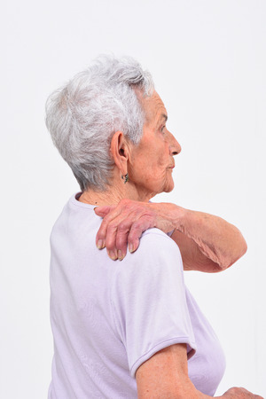 senior woman with pain on shoulder on white background Zdjęcie Seryjne
