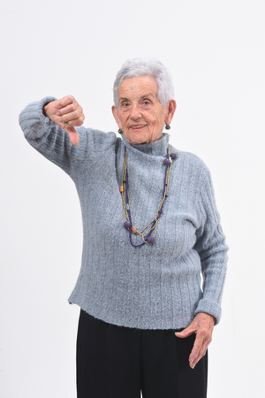 older woman holding her thumb down and smiling on white background