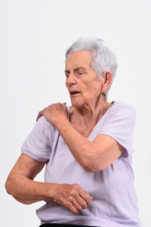 senior woman with pain on shoulder on white background Stock Photo