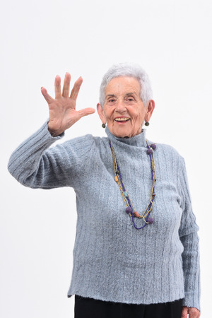 senior woman with open hand and number five on white background Stock Photo