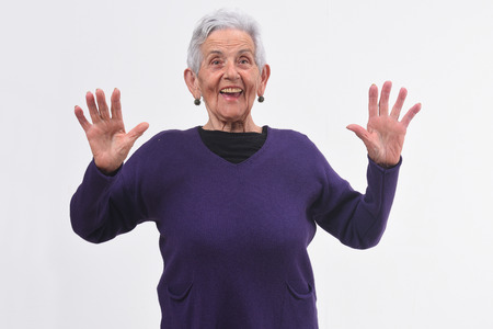 senior woman with a surprised face and raised hands on white background Stock Photo