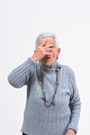 senior woman peeking with hand on face on white background Stock Photo