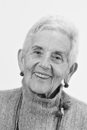 portrait of a senior woman smiling on white background, black and white