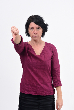 woman holding her thumb down and serious on white background