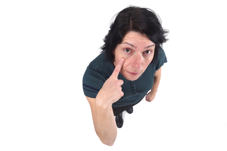 woman with finger on eye on white Stock Photo