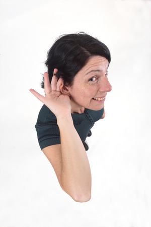 woman putting a hand on her ear because she can not hear on white background Stock Photo