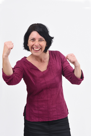 woman raising her arms and smiling in victory sign on white background Stock Photo