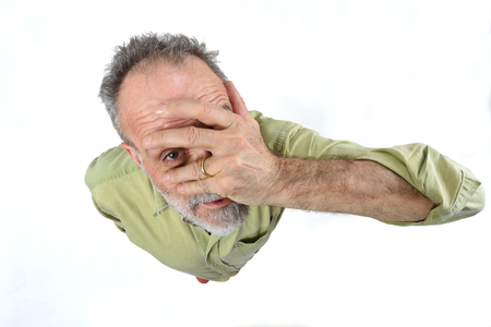 man peeking with hand on face on white background Stock Photo