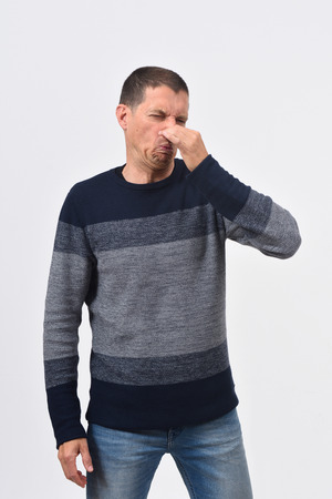 man who covers his nose with his fingers because it makes an smell bad