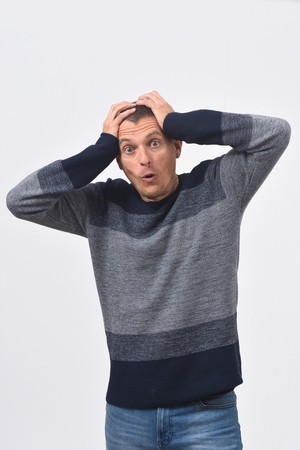 man with expression of forgetfulness or surprise on white background