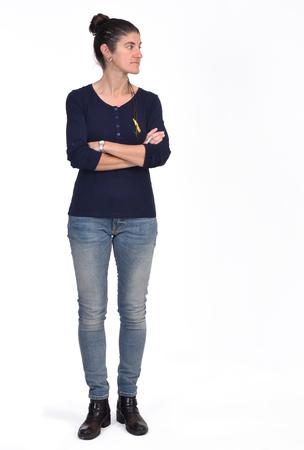 Retrato completo de una mujer con los brazos cruzados y mirando hacia el lado sobre fondo blanco.