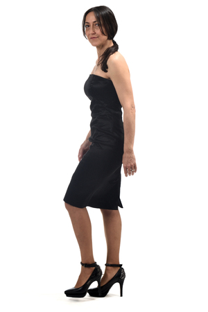 full portrait of a middle age woman walking with off the shoulder dress and heeled shoes isolated on white