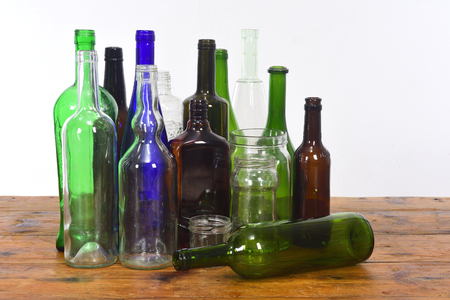 group of bottles and glass jars on a wooden table with white background