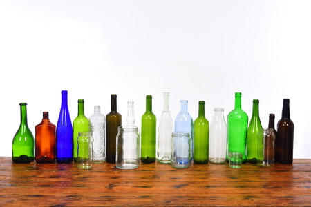 glass bottles and jars on top of a wooden table