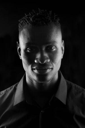 ritratto di un uomo africano su sfondo nero, serio, bianco e nero Archivio Fotografico
