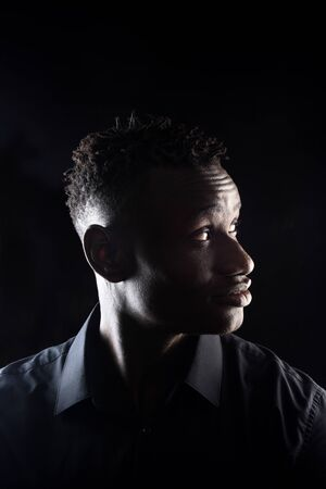 portrait of a african man on black background,profile