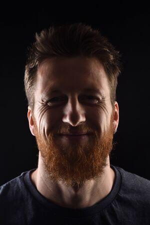 portrait of a smiling man on black background