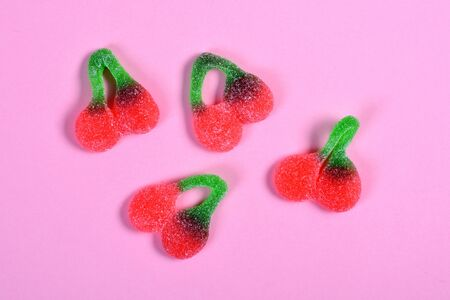 group of jelly candies cherries on pink background