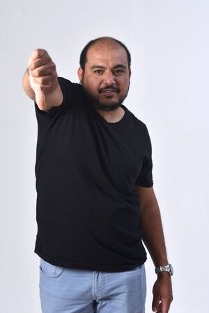 latin american man holding her thumb down and serious on white background