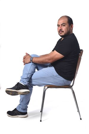 full portrait of a south american  man sitting on a chair on white