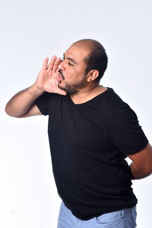 latin american man putting a hand in mouth and is screaming on white background