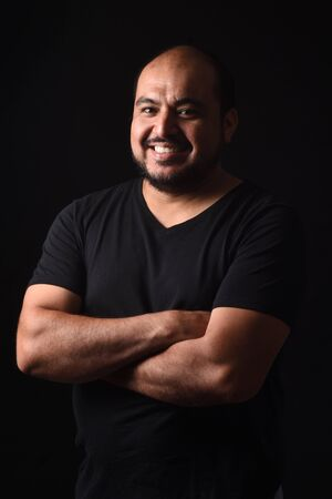 portrait  of a latin american man arms crossed on black background